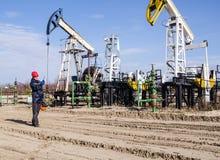 Ingegnere dell'uomo nel giacimento di petrolio Immagine Stock