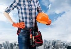 Ingegnere della donna che tiene un casco con toolbelt Fotografia Stock