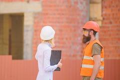 Ingegnere della donna e costruttore brutale barbuto discutere progresso della costruzione Discuta il piano di progresso Industria immagine stock