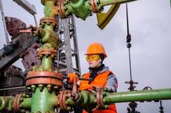 Ingegnere della donna nel giacimento di petrolio che ripara testa di pozzo Fotografie Stock