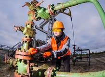 Ingegnere della donna nel giacimento di petrolio che ripara testa di pozzo Fotografia Stock