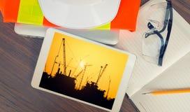 Ingegnere della tavola di funzionamento con la compressa e gli strumenti nell'affare di industria della raffineria di petrolio Fotografie Stock
