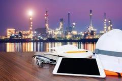 Ingegnere della tavola di funzionamento con la compressa e gli strumenti nell'industria della raffineria di petrolio Fotografia Stock