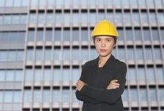Ingegnere delle donne asiatiche in braccio del ` s dell'incrocio uno sul backgr dei grattacieli Immagine Stock