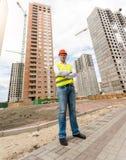 Ingegnere di costruzione che sta davanti alle costruzioni nell'ambito del const fotografia stock