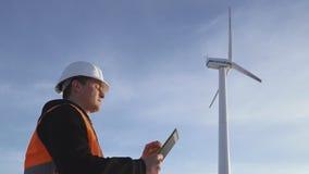 Ingegnere di energia del mulino a vento da lavorare con la compressa al tramonto ambientale video d archivio
