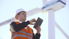 Ingegnere di energia del mulino a vento da lavorare con la compressa al tramonto ambientale stock footage