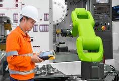 Ingegnere di manutenzione che collauda la macchina utensile robot automatica della mano con la macchina di CNC nell'industria aut fotografia stock