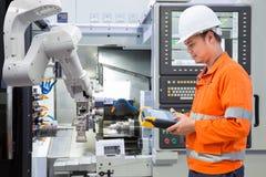 Ingegnere di manutenzione che programma robot automatizzato con CNC immagini stock libere da diritti