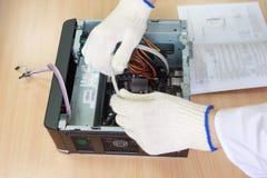 Ingegnere elettronico che fa un personal computer Istruzione per l'assemblea fotografia stock