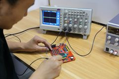 Ingegnere elettronico di Œmale del ¼ del ï del circuito e degli apparecchi elettronici che utilizza oscilloscopio nel laboratorio fotografie stock