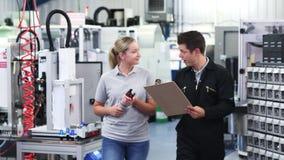 Ingegnere in fabbrica che discute componente con l'apprendista femminile stock footage