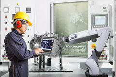 Ingegnere facendo uso della mano robot automatica di controllo di computer portatile con la macchina di CNC nell'industria automo immagine stock