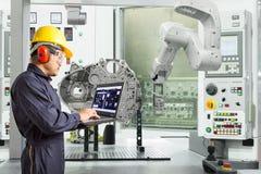 Ingegnere facendo uso della mano robot automatica di controllo di computer portatile con la macchina di CNC nell'industria automo fotografia stock