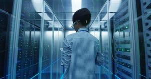 Ingegnere femminile etnico con la compressa che diagnostica l'hardware del server archivi video