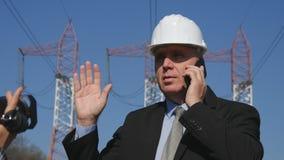 Ingegnere Filmed da un reporter Use Cell Phone che parla con il gruppo di manutenzione immagine stock libera da diritti