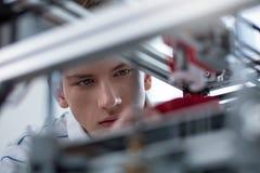 Ingegnere giovane bello che è messo a fuoco sulla stampa 3D Immagine Stock