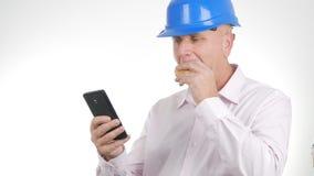 Ingegnere Image Eating un panino e un testo facendo uso del telefono cellulare immagine stock