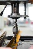 Ingegnere industriale che per mezzo di una macchina meccanica del trapano fotografie stock