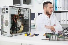 Ingegnere informatico che si siede con la console rotta Fotografie Stock