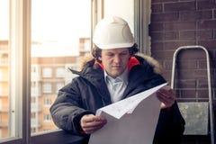Ingegnere lavorante in un casco bianco della costruzione con un progetto o un piano di disegno sui precedenti di un impianto indu fotografie stock