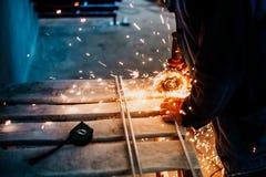 Ingegnere maschio meccanico che lavora nella fabbrica facendo uso di una smerigliatrice di angolo per acciaio, ferro o metallo ta immagini stock