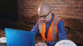 Ingegnere maschio nel funzionamento di vetro con il computer portatile nella stanza Il casco di sicurezza bianco si trova sulla t stock footage