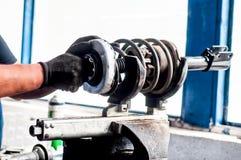 Ingegnere meccanico automatico che regola un ammortizzatore automatico fotografie stock
