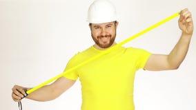 Ingegnere o architetto di costruzione felice in maglietta e casco gialli facendo uso del nastro di misura contro fondo bianco Fotografie Stock Libere da Diritti