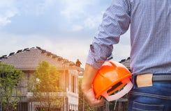Ingegnere residente che tiene il casco di sicurezza giallo alla nuova costruzione domestica Immagine Stock Libera da Diritti