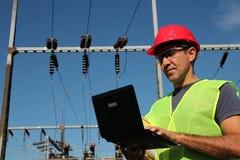 Ingegnere Using Laptop ad una sottostazione elettrica. Fotografia Stock Libera da Diritti
