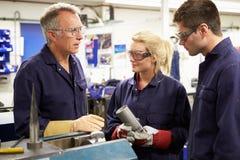Ingegnere Working With Apprentices sul pavimento della fabbrica Immagine Stock