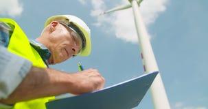 Ingegnere Writing On Clipboard mentre facendo ispezione del generatore eolico archivi video