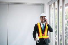 Ingegneri asiatici dell'uomo facendo uso del telefono cellulare e del modello di tenuta in ufficio fotografie stock