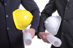 Ingegneri che giudicano il casco e la mappa di sicurezza pronti per lavorare Fotografia Stock