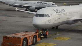 Ingegneri del Groundcrew che ispezionano il trattore di Push-Back che rimorchia attrezzatura da un aeroplano di Lufthansa Airbus  stock footage