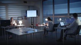 Ingegneri di sviluppo di elettronica in camice che lavorano ai personal computer nel laboratorio di elettronica video d archivio