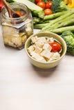 Ingelegde Gedobbelde feta-kaas in olijfolie en groenten op witte houten achtergrond, grens Royalty-vrije Stock Afbeeldingen