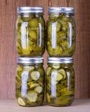 Ingelegde komkommers in pekel in metselaarkruiken Stock Afbeelding