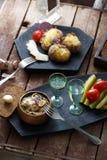 Ingelegde tomaten, komkommers, paddestoelen en ui op houten achtergrond met vork en schoten van wodka Royalty-vrije Stock Afbeeldingen