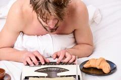 Ingen dag utan kapitel Tappningskrivmaskinsbegrepp Man som skriver den retro skrivande maskinen Gammal skrivmaskin på sängkläder  arkivbild