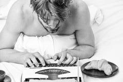 Ingen dag utan kapitel Tappningskrivmaskinsbegrepp Man som skriver den retro skrivande maskinen Gammal skrivmaskin p? s?ngkl?der  arkivbilder