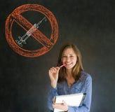 Ingen drogkvinna som ler pennan och den pappers- handen på hakan på svart tavlabakgrund Arkivfoton