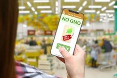 Ingen GMO idé, flicka med den frameless telefonen på suddigt shoppar bakgrund Fotografering för Bildbyråer
