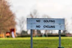 Ingen inte tillåtna golfspel och ingen cykla teckenstolpe att spela i detta område, där var tecken: Spela inte golf och cykla int Royaltyfria Bilder