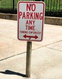 Ingen parkering när som helst och att bogsera det upprätthöll tecknet framme av en regerings- byggnad Royaltyfri Foto