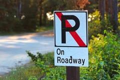 Ingen parkering på körbanatecken med en väg i bakgrunden Arkivbilder