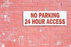 Ingen parkering 24 timme-timmetillträde krävde tecknet på den stora stora väggen för röd tegelsten UK royaltyfri foto