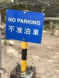 Ingen parkering undertecknar in både kines och engelska Arkivbild