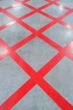 Ingen parkeringsRöda korsetzon, criss-kors målade på polerat golv Royaltyfri Bild